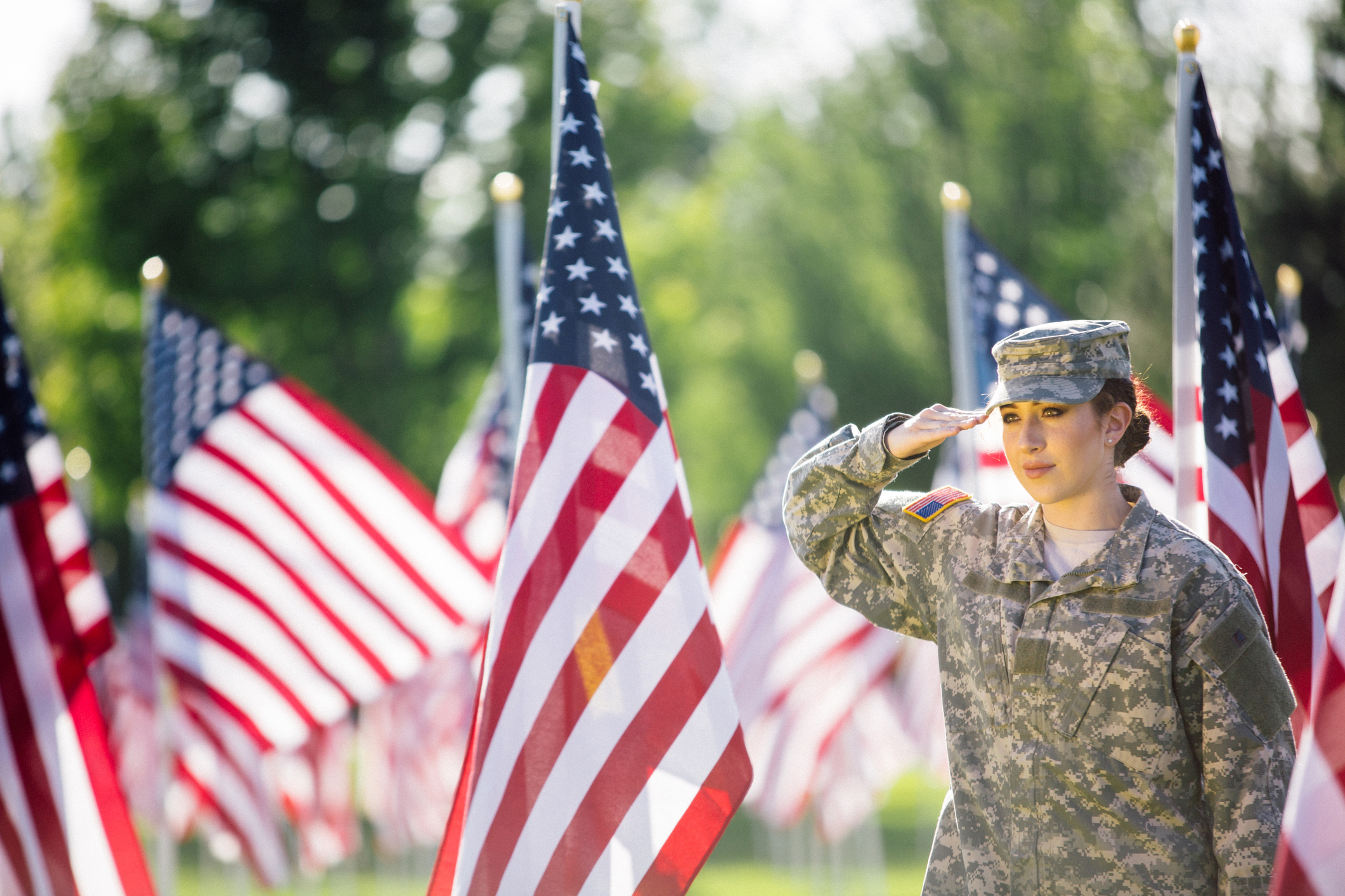A young service woman salutes amid a field of American flags.