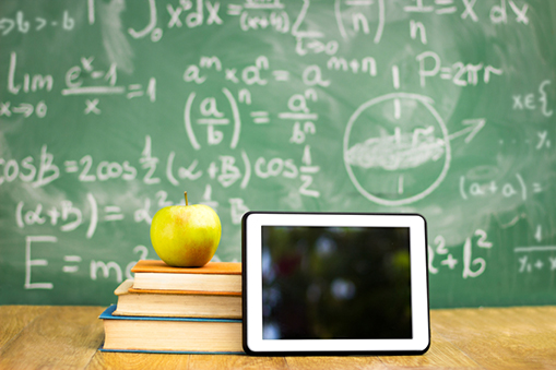 An iPad next to stacked books with an apple on top all in front of a blackboard with complex formulas.