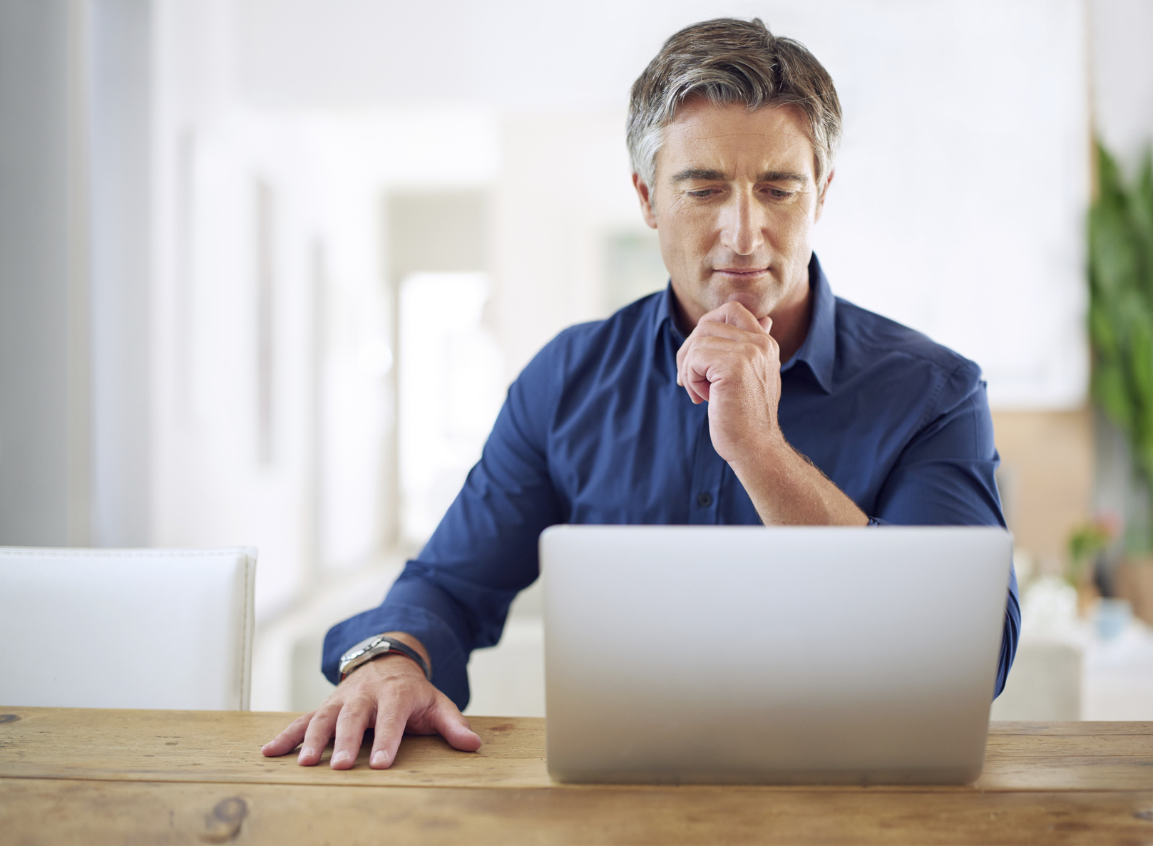Man looking at a laptop computer screen and thinking