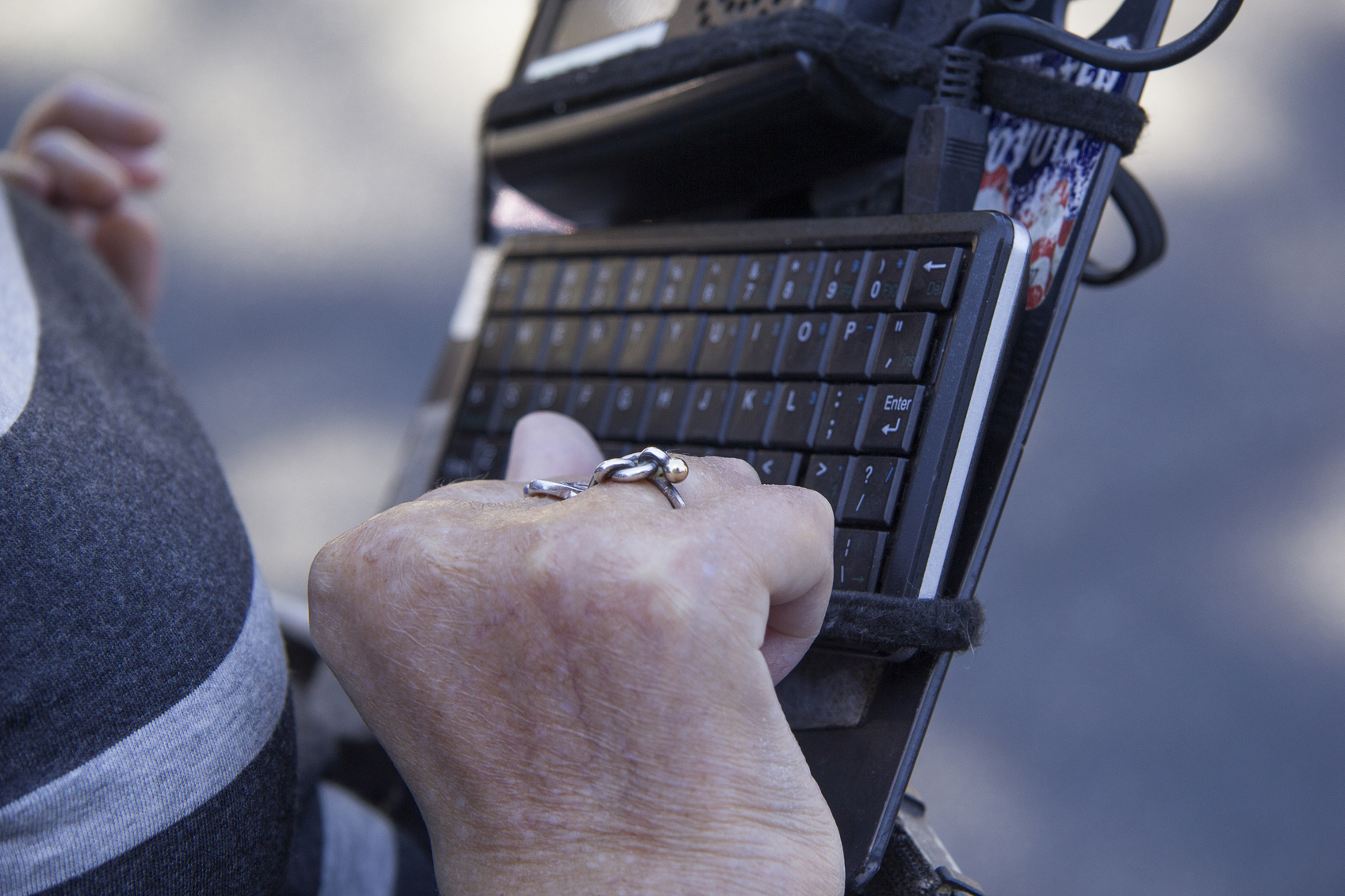 Photo of a hand with folded fingers in front of a keyboard attached to a wheelchair.